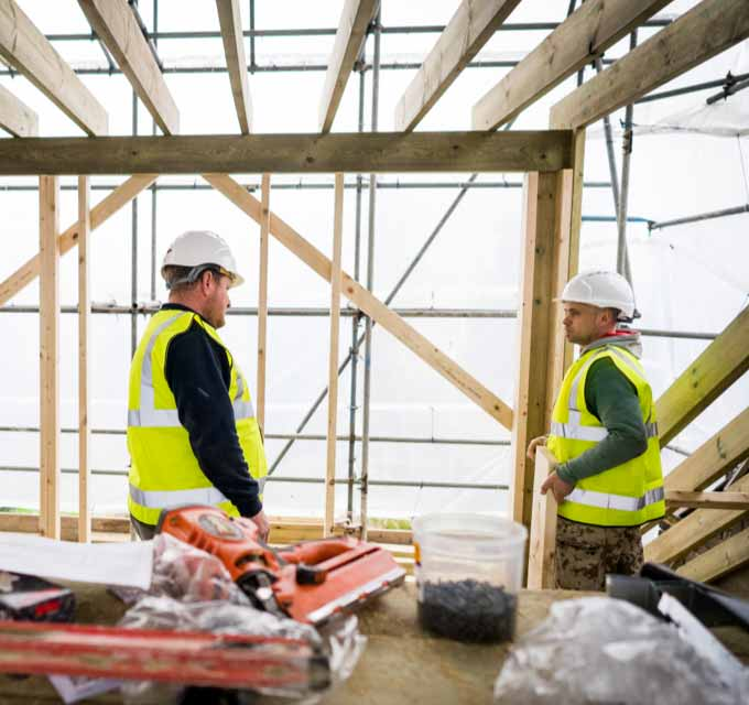 Tradesmen in discussion on a lofty building site
